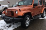 This Orange 4 door Sahara SUV features a Black interior  a  3.8L  V 6 engine, and has 40891 kilometres on it.