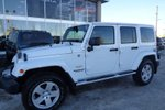 This White 4 door Sahara - 4x4! Topless Fun! Hard @ Soft Tops! SUV features  a 6 Spd Manual transmission, a  3.6L  V 6 engine, and has 54789 kilometres on it.